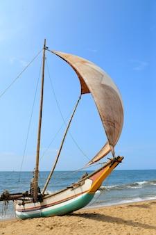 Fischerboote, die auf leerem strand in sri lanka ruhen