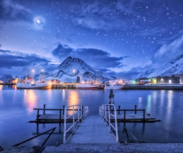Fischerboote nahe pier auf dem meer gegen schneebedeckte berge und sternenhimmel mit mond bei nacht in den lofoten-inseln, norwegen.