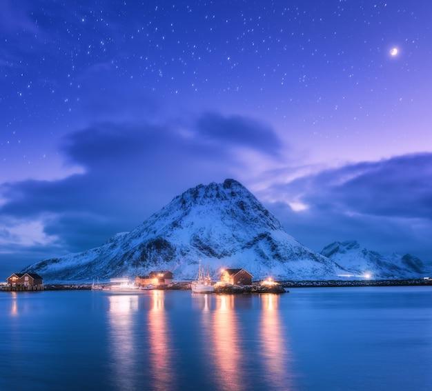 Fischerboote nahe pier auf dem meer gegen schneebedeckte berge und sternenklaren lila himmel mit mond bei nacht