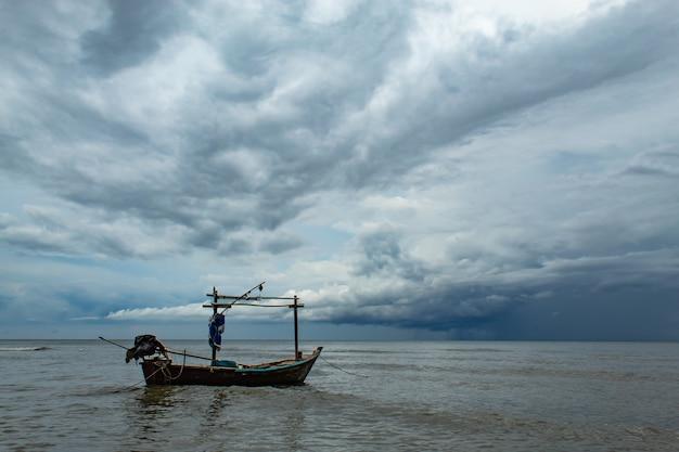Fischerboote und der regen, der in das meer fällt.