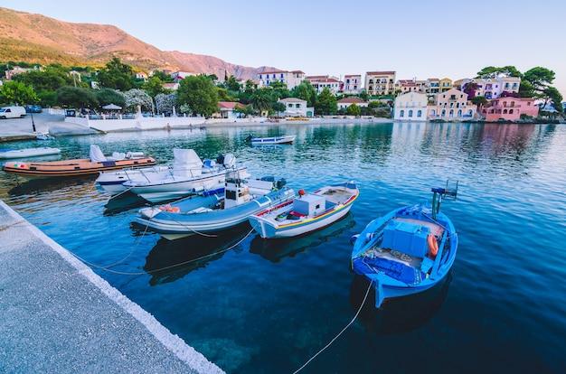 Fischerboote vor anker in der seebucht des dorfes assos in der schönen azurblauen bucht in kefalonia, griechenland