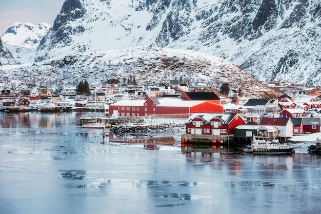 Fischerdorf von reine auf eisiger küstenlinie mit schneebedecktem berg