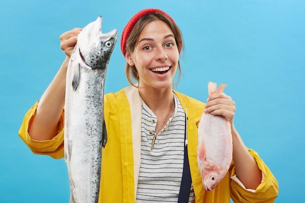 Fischerin, die zwei frisch gefangene seefische in ihren händen anbietet