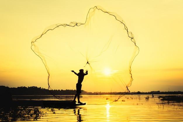 Fischermann, der badnetzfischen am see mit hintergrund des berges und des blauen himmels thowing ist