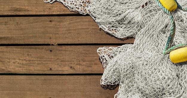 Fischernetz auf hölzernem decking-hintergrund mit kopienraum