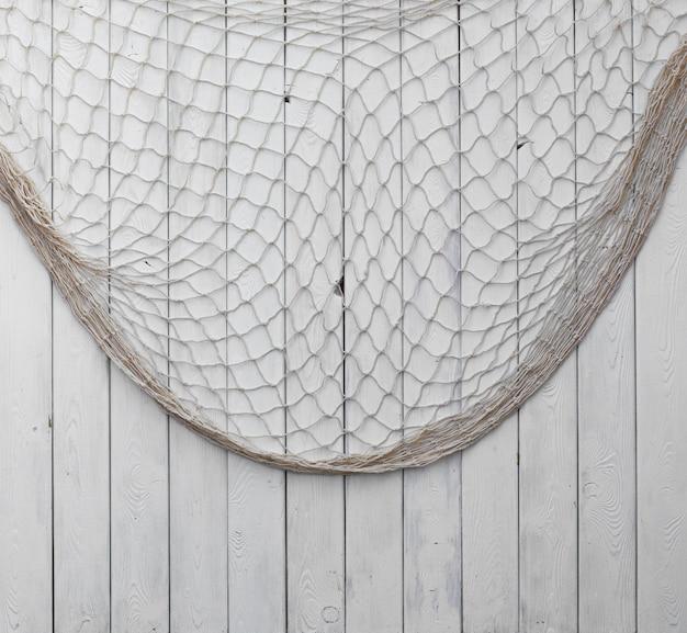 Fischernetz auf weißem holzhintergrundhintergrund für text oder bild