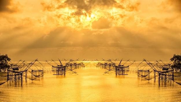 Fischerwerkzeug mit sonnenaufgang mit orangefarbenem himmel bei pakpra, phatthalung, thailand