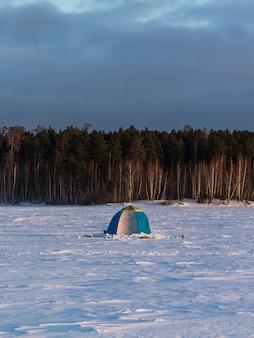 Fischerzelt auf einem zugefrorenen verschneiten see. im dichten wald