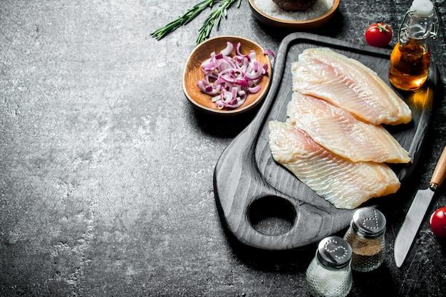 Fischfilet auf einem schneidebrett mit gehackten zwiebeln in einer schüssel und gewürzen. auf schwarz rustikal