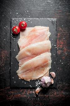 Fischfilet auf papier auf einem steinbrett mit knoblauch und tomaten. auf dunkler rustikaler oberfläche