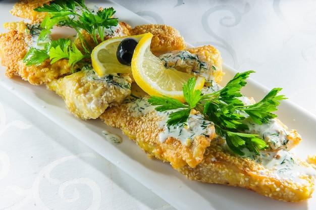 Fischgericht - gebratenes fischfilet mit gemüse auf weißem hintergrund
