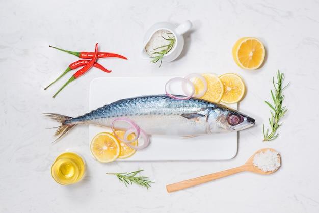 Fischgericht kochen mit verschiedenen zutaten. frischer roher fisch dekoriert mit zitronenscheiben und kräutern auf holztisch.