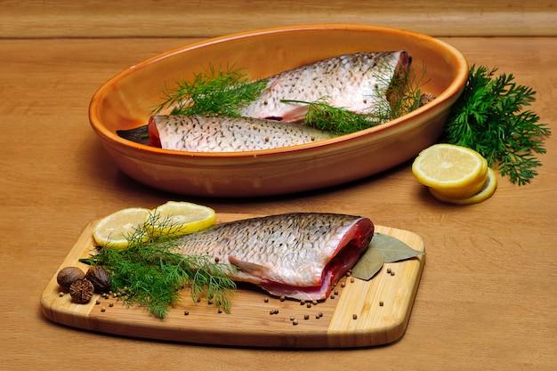 Fischkadaver mit gewürzen auf hölzerner hartfaserplatte, zum kochen vorbereitet