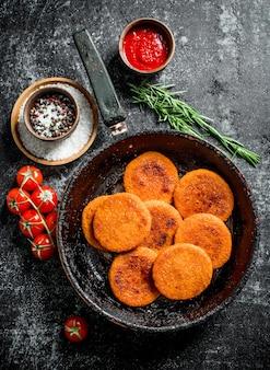 Fischkoteletts in einer pfanne mit gewürzen, sauce, rosmarin und tomaten. auf schwarzem rustikalem hintergrund