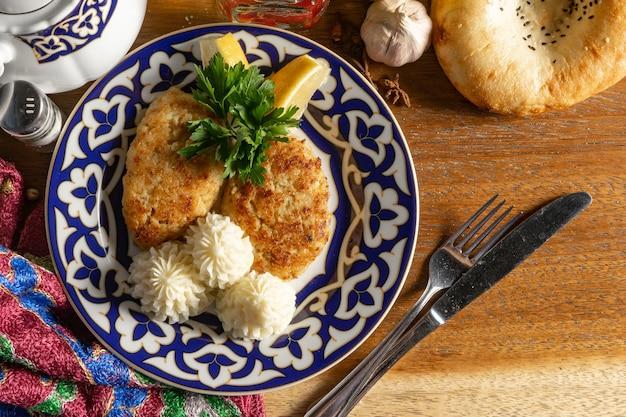 Fischkoteletts mit kartoffelpüree, zitrone und petersilie in einem teller mit einem traditionellen usbekischen muster.