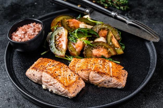 Fischmahlzeit mit gebratenen lachsfiletsteaks und rucola-tomatensalat auf einem teller. schwarzer hintergrund. ansicht von oben.