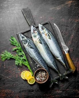 Fischmakrele auf einem schneidebrett mit zitronenscheiben, dill und gewürzen. auf dunklem rustikalem tisch