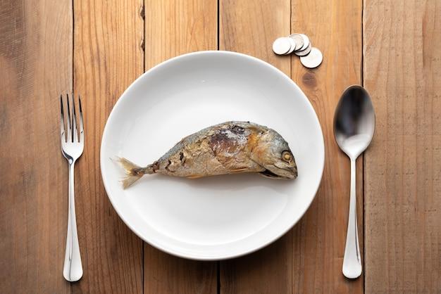 Fischmakrele gezeigt auf platte mit löffel, völkern und münzen
