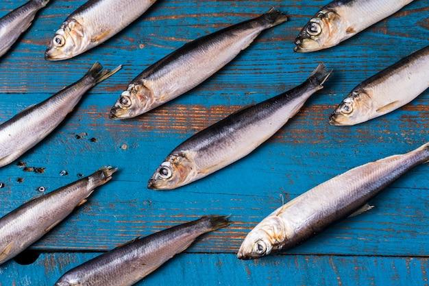 Fischmuster. heringfische auf einem alten blauen hölzernen hintergrund.