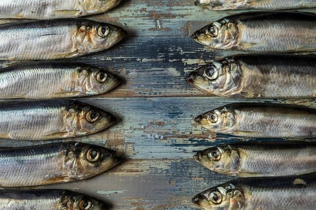 Fischmuster heringsfische auf einem alten blauen hölzernen hintergrund.