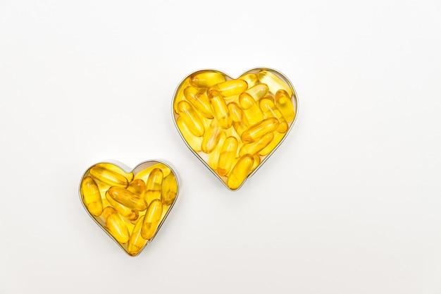 Fischölkapseln in einer herzformboxen auf weißem hintergrund, vitamin d-ergänzung, gesundheitskonzept, draufsicht
