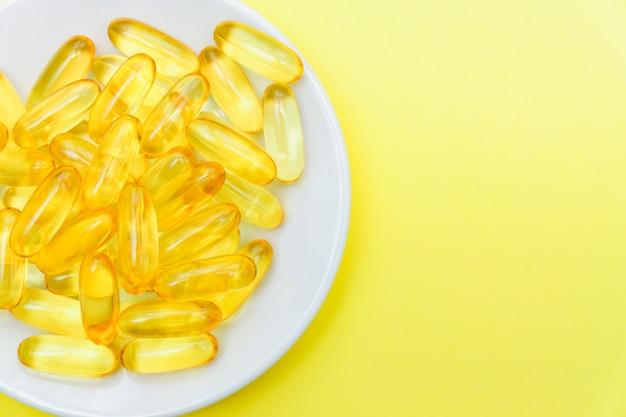 Fischölkapseln in einer weißen platte auf gelbem hintergrund. draufsicht, flache lage, kopierraum.