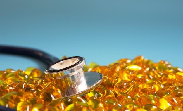 Fischölkapseln mit stethoskop auf blauem hintergrund. gesundes omega-3 und stethoskop.