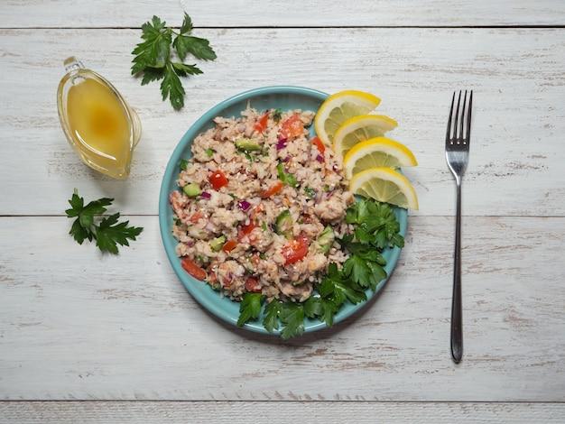Fischsalat mit reis auf einem weißen holztisch. grüner bio-salat mit thunfischscheiben. draufsicht.