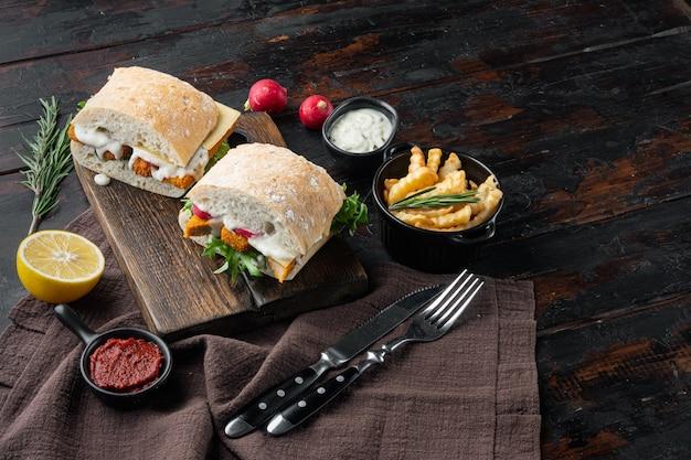 Fischstäbchen-sandwich-set, auf holzschneidebrett, auf altem dunklem holztisch