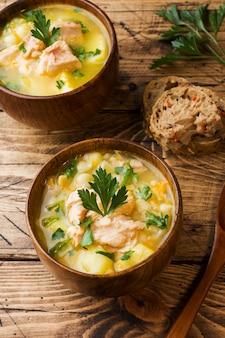 Fischsuppe in einer holzschale mit frischen kräutern.