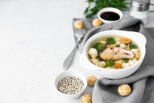 Fischsuppe mit rosa lachs, blumenkohl und brokkoli in einer weißen schüssel