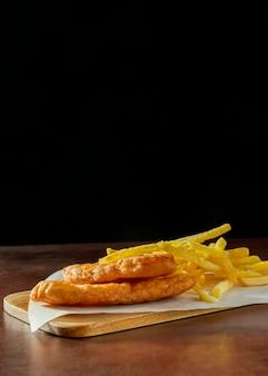 Fish and chips auf schneidebrett mit kopierraum