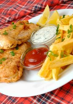 Fish and chips, mayo und ketchup auf roter tischdecke