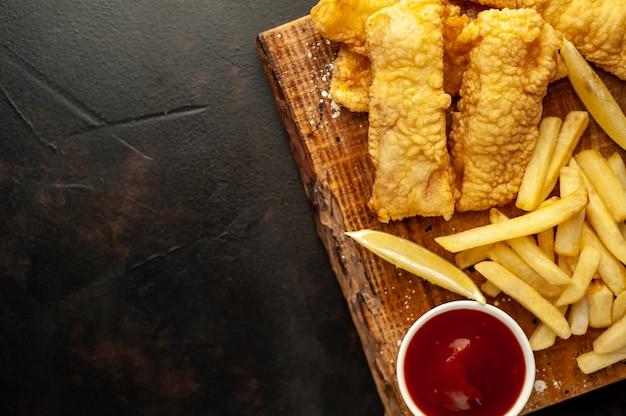 Fish and chips mit pommes frites, auf einem steinhintergrund mit kopierraum für ihren text