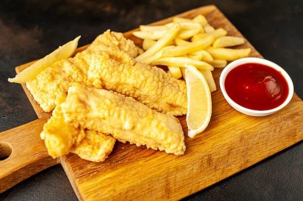 Fish and chips mit pommes frites auf einem steinhintergrund
