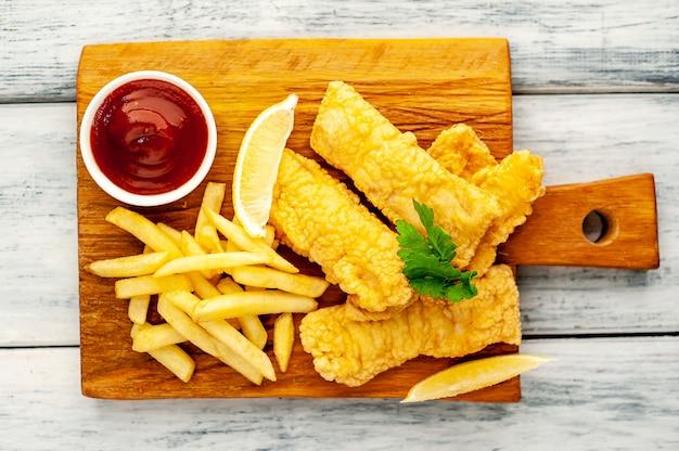 Fish and chips mit pommes frites auf holzhintergrund