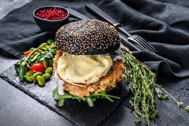 Fishburger mit schwarzem briochebrötchen, omelett, fischkotelett und rucola. schwarzer hintergrund. draufsicht