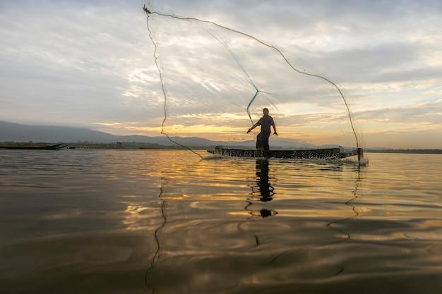 Fishermen casting geht in den frühen morgenstunden mit holzbooten, alten laternen und netzen angeln. lebensstil des konzept-fischers.