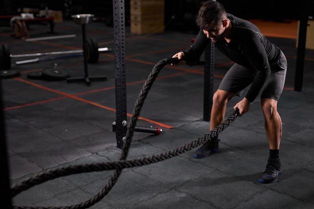 Fit athlet, der kampfseilübung im cross-fit-fitnessstudio macht und intensives training alleine hat. konzentrierter kaukasischer mann, der cross-fit-übung macht, während er im fitnessstudio, in sportbekleidung trainiert.