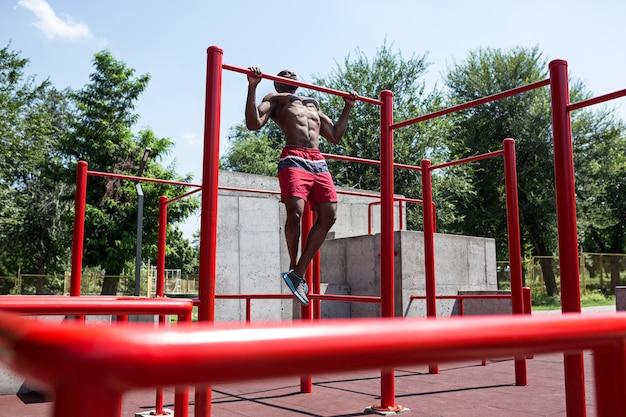 Fit athlet macht übungen im stadion. afro oder afroamerikanermann im freien an der stadt