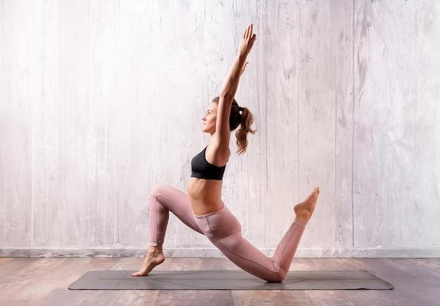Fit attraktive muskulöse junge blonde frau, die eine yoga-pose mit geringer longe-variation auf einer matte macht