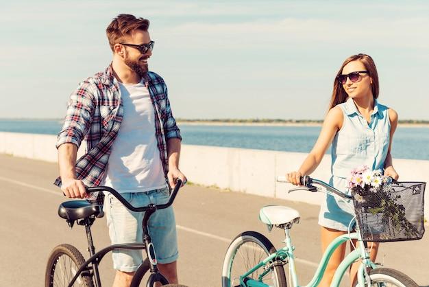 Fit bleiben und spaß haben. glückliches junges paar, das seine fahrräder rollt und sich beim gehen im freien mit einem lächeln ansieht?