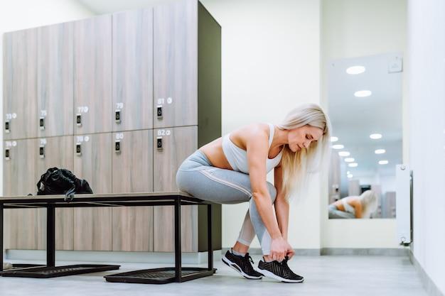 Fit blonde frau, die sportbekleidung im umkleideraum trägt, bereitet sich auf fitness-training vor.