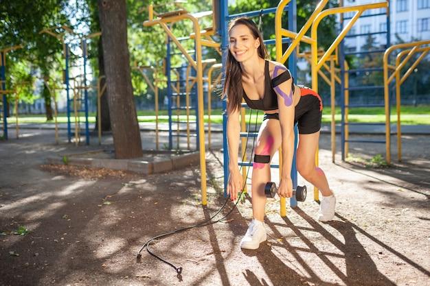 Fit brunette wunderschöne frau training mit hantel im park, sportplatz. junge frau mit elastischem taping beim körpertraining im freien. rehabilitation, kinesiotherapeutisches behandlungskonzept.