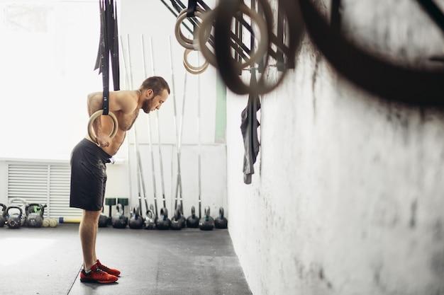 Fit dip ring mann bereiten sich auf das training im fitnessstudio tauchübung vorbereiten