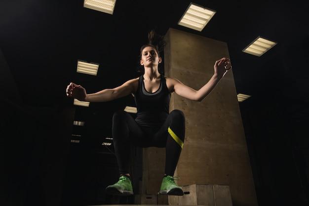 Fit frau beim boxspringen im crossfit-fitnessstudio