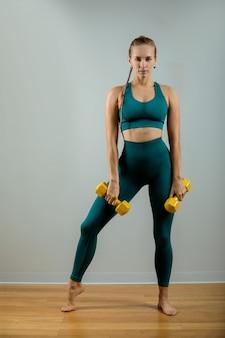 Fit frau beim heben von gewichten. schönes fitness-mädchen auf einem grauen hintergrund, der mit hanteln auf einem grauen hintergrund aufwirft.