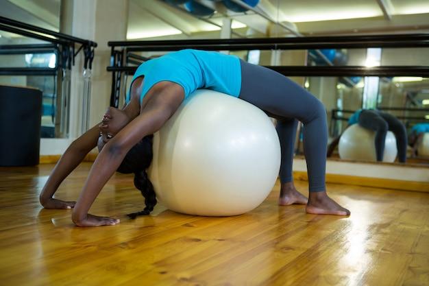 Fit frau, die auf fitnessball trainiert