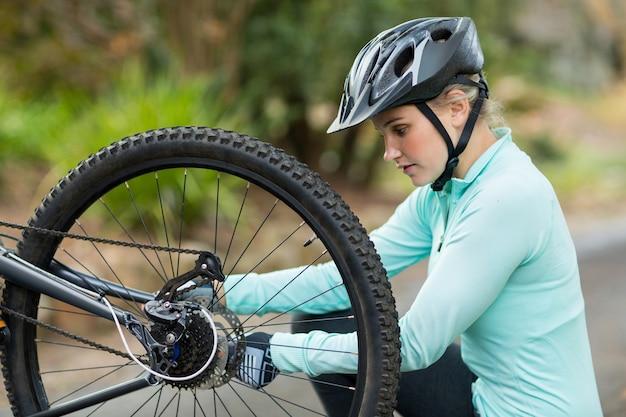 Fit frau, die die kette an ihrem fahrrad befestigt
