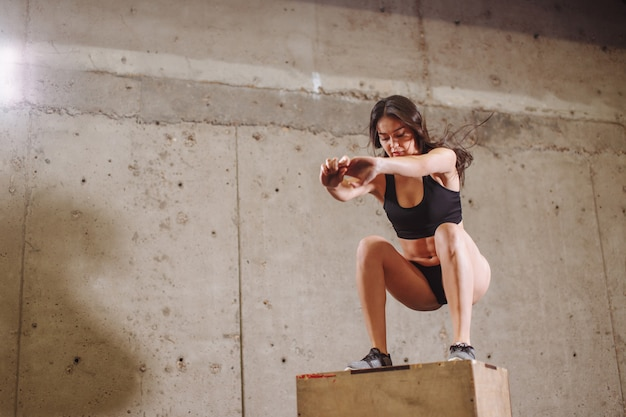 Fit frau, die eine boxsprungübung macht. muskulöse frau, die eine box squat im fitnessstudio tut